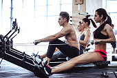 Group of sporty muscular people are working out in gym. gym training. Paddling training apparatus. Side view of four sportsmen are rowing together.