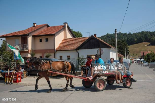 A group travels through the town by a horse drawn cart during the Guca Trumpet Festival on August 12 2017 in Guca Serbia Thousands of revellers...