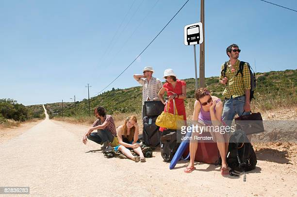group waiting at a bus stop on long deserted road