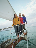 Group women standing on bow of sailboat, laughing, portrait