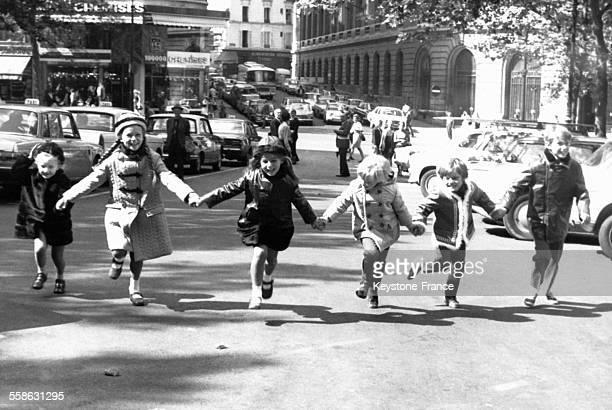 Groupe d'enfants présentant pour la rentrée scolaire une ligne de manteaux du couturier Mainett inspirée par les évènements de mai 68 à Paris France...
