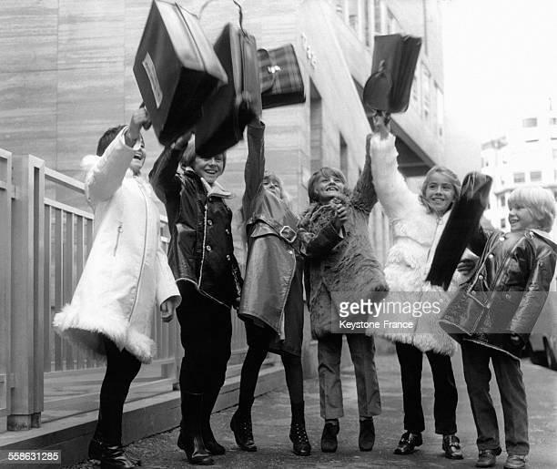 Groupe d'enfants présentant une ligne de manteaux pour la rentrée scolaire à Paris France le 8 septembre 1970