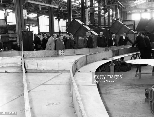 Groupe d'invités devant la réalisation du gigantesque stabile 'Homme' en acier inoxydable d'Alexandre Calder aux ateliers des établissements Biémont...