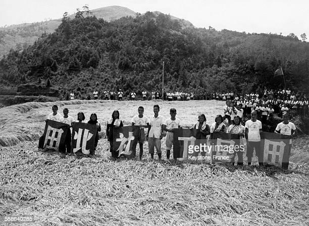 Groupe d'ouvriers agricoles photographiés après avoir fait le record de récolte de riz à la coopérative en Chine en septembre 1958