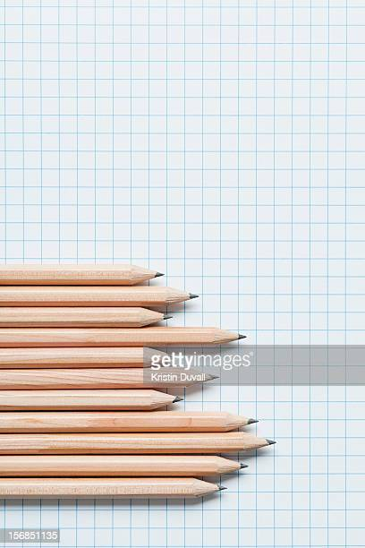 Grouping of wooden pencils in graph shape on graph paper