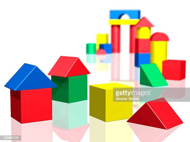 Groups of colourful building blocks set up as towers and houses, 3-D cutout
