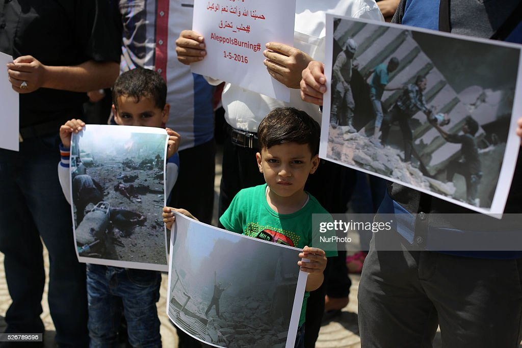 Groups of Syrian refugees hold slogans during a protest against Syrian President Bashar al-Assad in gaza city, May 1, 2016 . At least 34 people were killed by shelling and missile fire in the Syrian city of Aleppo, the largest in the north of the country, the Syrian Observatory for Human Rights, or SOHR, reported on 28 April. Among those were at least 20 people killed by the airstrikes of warplanes, the identity of which is still unknown, in the neighborhoods of Bustan al-Qasr and al-Kalasa, according to SOHR.
