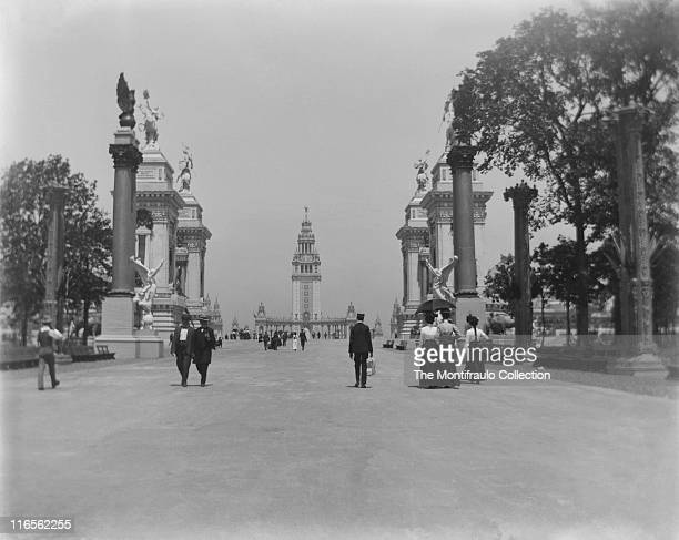 Groups of visitors passing through the centrepiece of the Gateway of the Triumphal Bridge at the PanAmerican Exposition World Fair which leads to the...