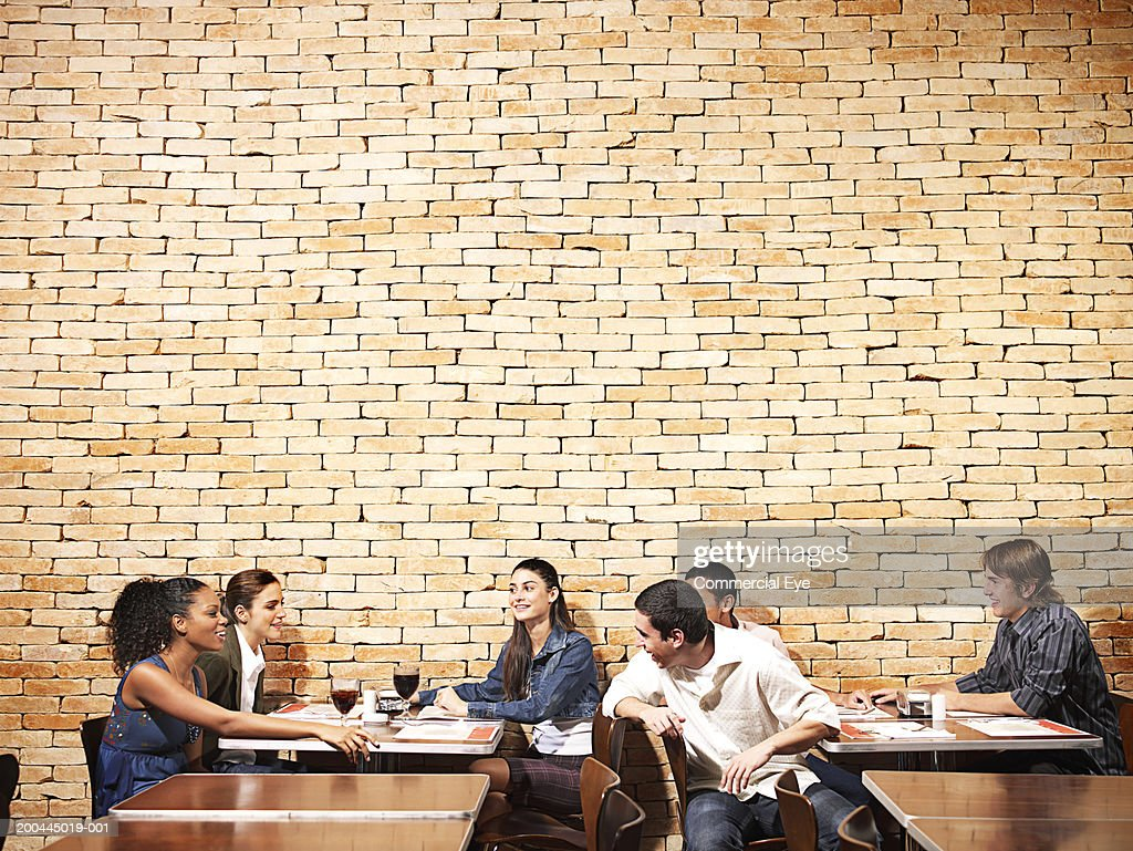 Groups of young men and women flirting in restaurant : Stock Photo