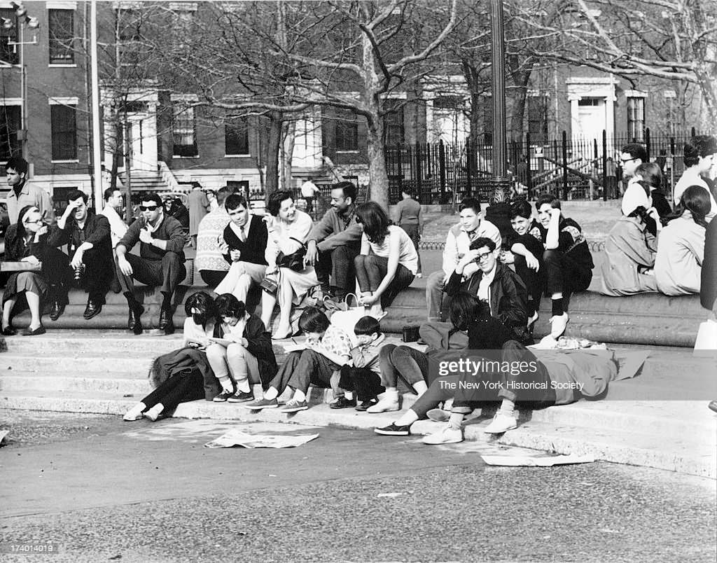Groups of young men and women sit on the steps leading down to the fountain Washington Square Park with Washington Square North seen through trees...
