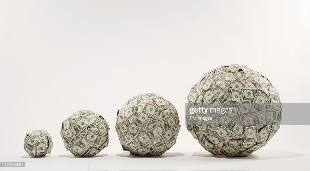 Growing balls of money : Stock Photo