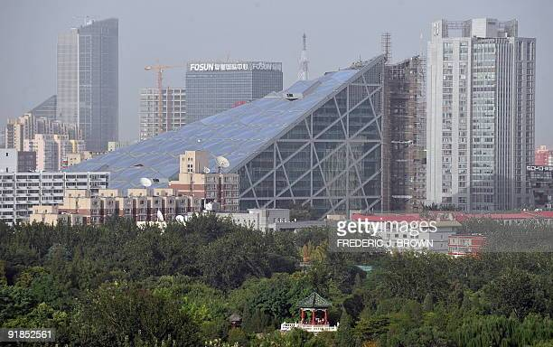 A growing skyline of new buildings in Beijing stands before Ritan Park where people are gathered in a traditional Chinese pavilion atop a hill on...