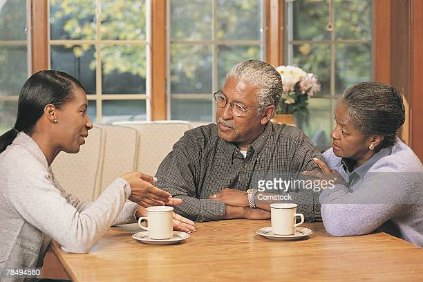 Grown daughter talking to parents at home