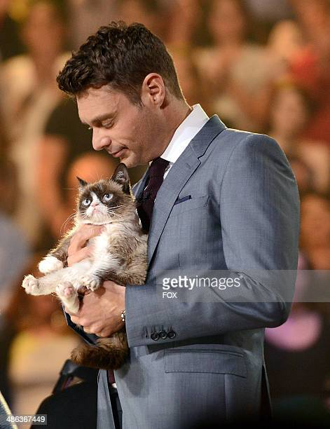 Grumpy Cat and host Ryan Seacrest onstage at FOX's 'American Idol XIII' Top 6 Live Performance Show on April 23 2014 in Hollywood California