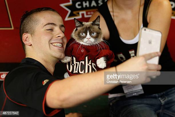 'Grumpy Cat' poses for a selfie with a fan before the MLB game between the Arizona Diamondbacks and the San Francisco Giants at Chase Field on...