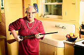 A grumpy granny in curlers and cat glasses holding a rifle in her kitchen near the sink. More granny images.