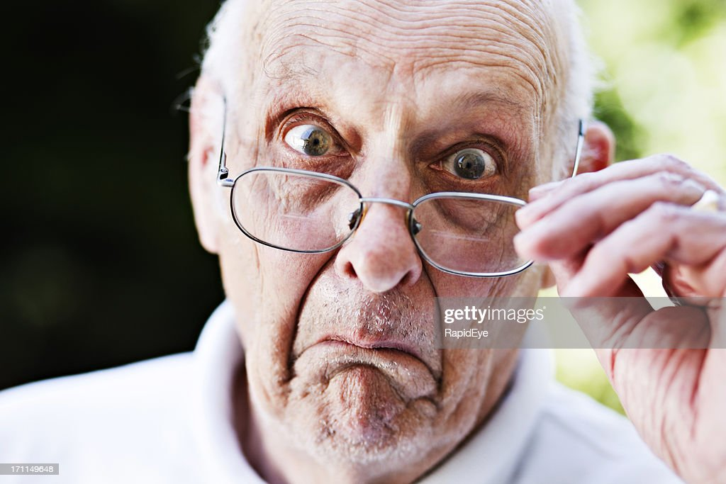 Grumpy old man looks over spectacles, shocked and disapproving
