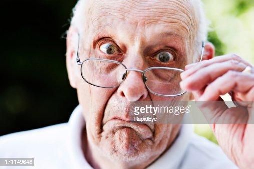 Grumpy old man sieht mit Brille ist überrascht und nicht sehr erfreut darüber