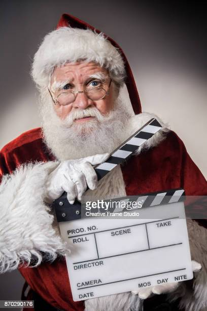 Grumpy Santa Claus holding a film clapperboard