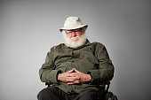 Portrait of grumpy senior man sitting on wheelchair looking at camera against grey background