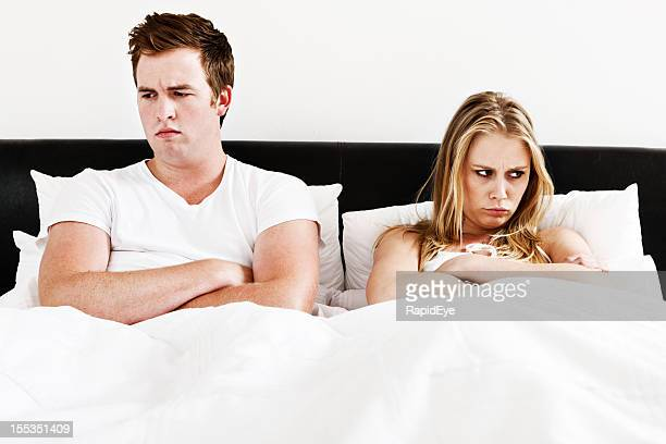 Grumpy young couple sulking in bed after an argument