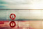 Grunge cruise deck background at dawn.Lifebuoy hand railing deck. Vintage look.