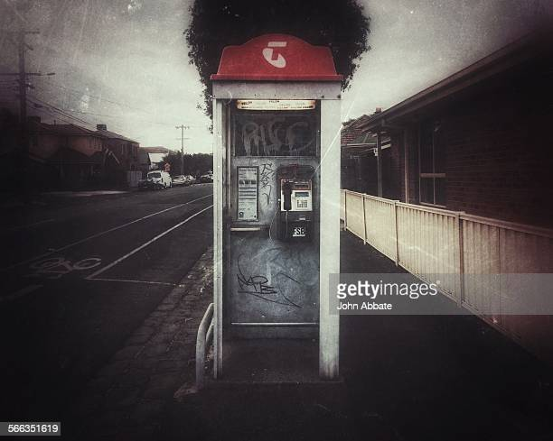 grunge filtered image of an old fulllength Telstra phone booth in a suburban Melbourne street