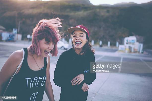 Grunge girls laughing together in a parking lot