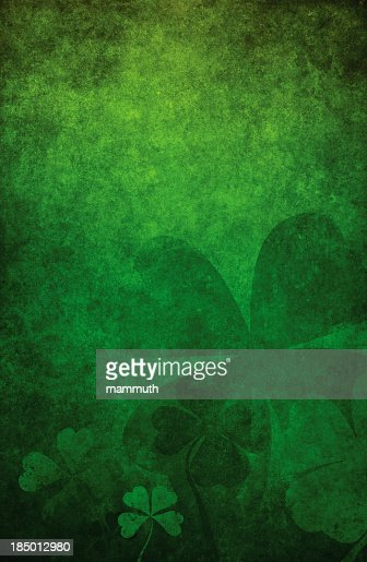 Grunge green background with four leaf clovers