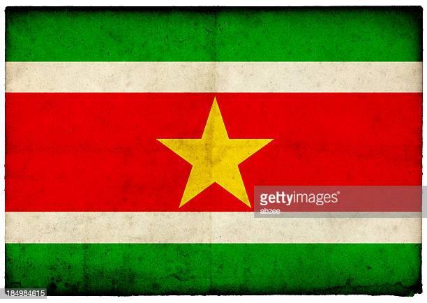 Grunge Suriname Flag on rough edged old postcard