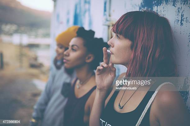 Grungy teen with pink hair hanging out smoking with friends
