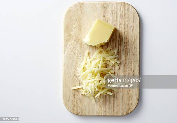 Gruyere, partially grated, on chopping board, overhead view