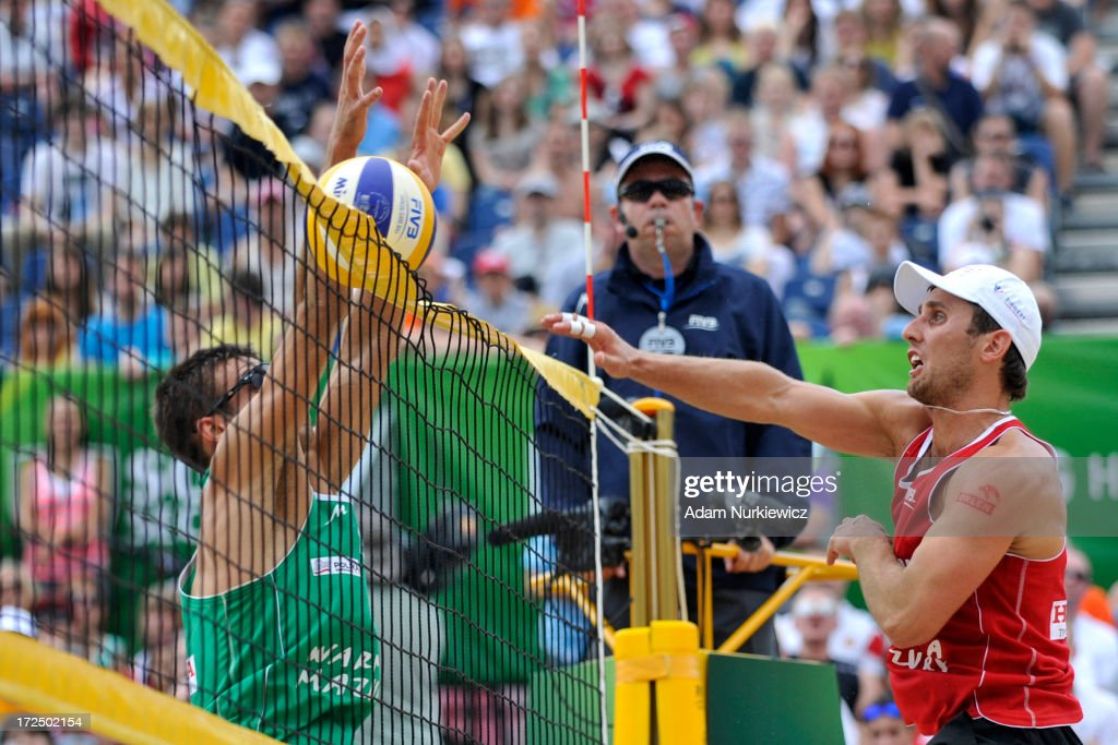 Grzegorz Fijalek (R) of Poland attacks against Javier Monfort Minaya (L) of Spain during Day 2 of the FIVB World Championships on July 2, 2013 in Stare Jablonki, Poland.
