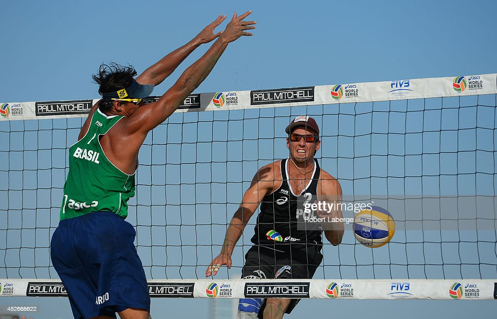 Grzegorz Fijalek of Poland (right) spikes the Mikasa against Ricardo Santos of Brazil during the FIVB Long Beach Grand Slam on July 25, 2014 in Long Beach, California.
