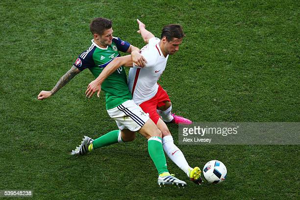 Grzegorz Krychowiak of Poland and Oliver Norwood of Northern Ireland compete for the ball during the UEFA EURO 2016 Group C match between Poland and...