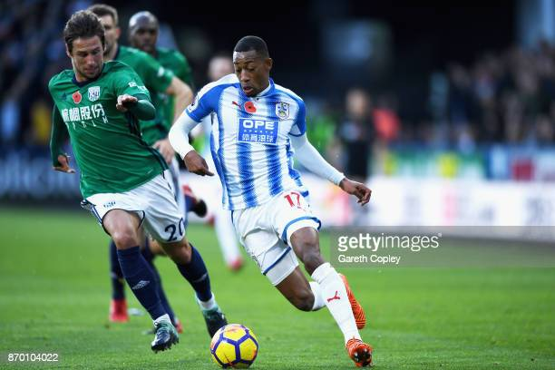 Grzegorz Krychowiak of West Bromwich Albion and Rajiv van La Parra of Huddersfield Town battle for possession during the Premier League match between...