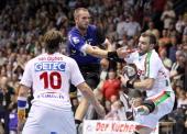 Grzegorz Tkaczyk of Magdeburg is challenged by Fabian van Olphen and Bartosz Jurecki of Rhein Neckar Loewen during the Toyota Handball Bundesliga...