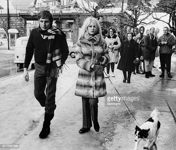 French actress Brigitte Bardot and her husband Gunther Sachs walk their dog through the streets of Gstaad watched by curious onlookers The couple is...