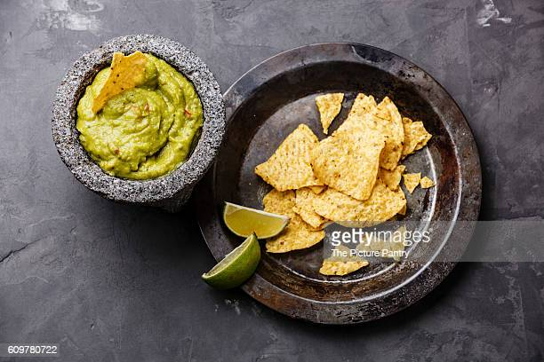 Guacamole fresh dip with nachos chips on gray concrete stone background