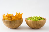 Guacamole in a wooden bowl and nachos isolated on white background