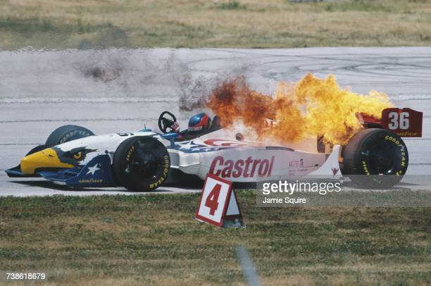 Gualter Salles of Brazil climbs out of the burning All American Racers Eagle 997 Toyota during the Championship Auto Racing Teams 1999 FedEx...