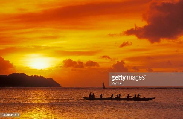 outrigger canoe paddlers at sunset at Tumon Bay resort area