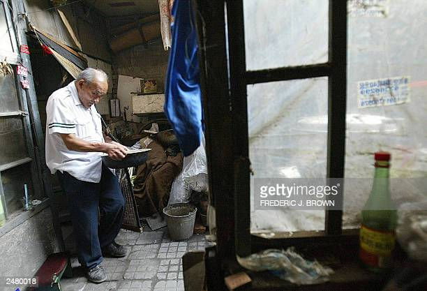 Guan Daoli carries a basin of water in his courtyard home in central Beijing 08 September 2003 Guan whose family have resided here since his Manchu...