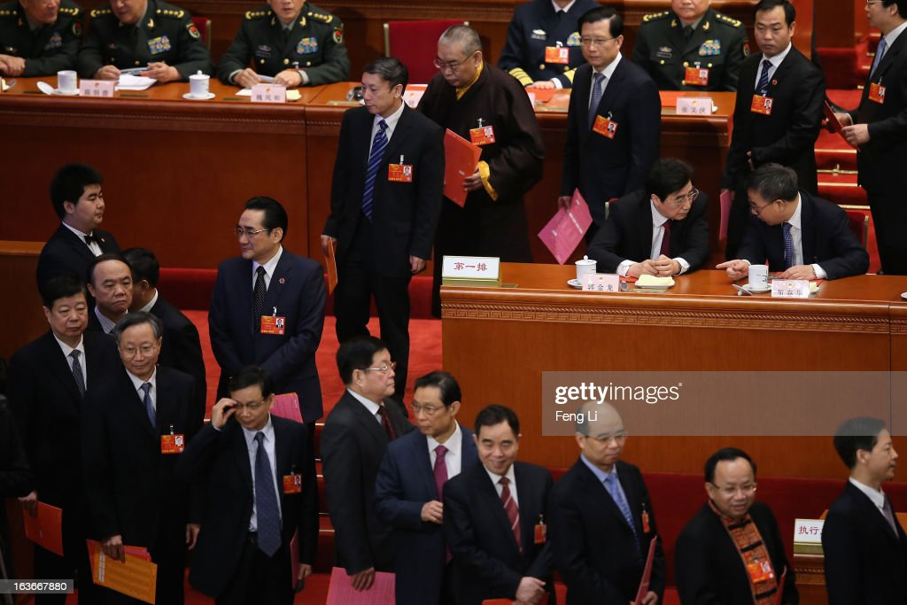 Guangdong Communist Party Secretary Hu Chunhua (R) talks with Beijing Municipal Communist Party Secretary Guo Jinlong (L) as delegates waiting to cast their votes into a box during the fourth plenary meeting of the National People's Congress (NPC) at the Great Hall of the People on March 14, 2013 in Beijing, China. Xi Jinping, general secretary of the Communist Party of China Central Committee, was elected President of the People's Republic of China and Chairman of the Central Military Commission on Thursday.