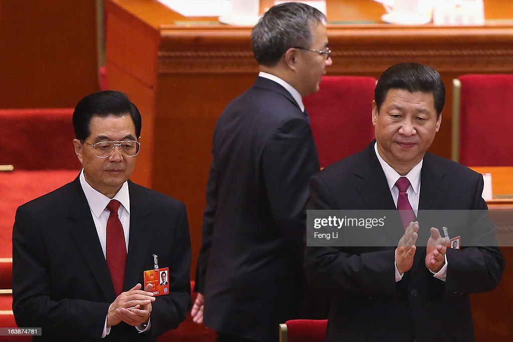 Guangdong Communist Party Secretary Hu Chunhua (C) walks past former Chinese president Hu Jintao (L) and the newly-elected President Xi Jinping (R) at the closing session of the National People's Congress (NPC) at the Great Hall of the People on March 17, 2013 in Beijing, China. China's newly-elected president Xi Jinping pledged Sunday to resolutely fight against corruption and other misconduct in all manifestations.