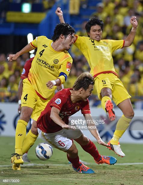 Guangzhou Evergrande defender Feng Xiaoting fights for the ball against Kashiwa Reysol defender Daisuke Suzuki and forward Masato Kudo during the AFC...