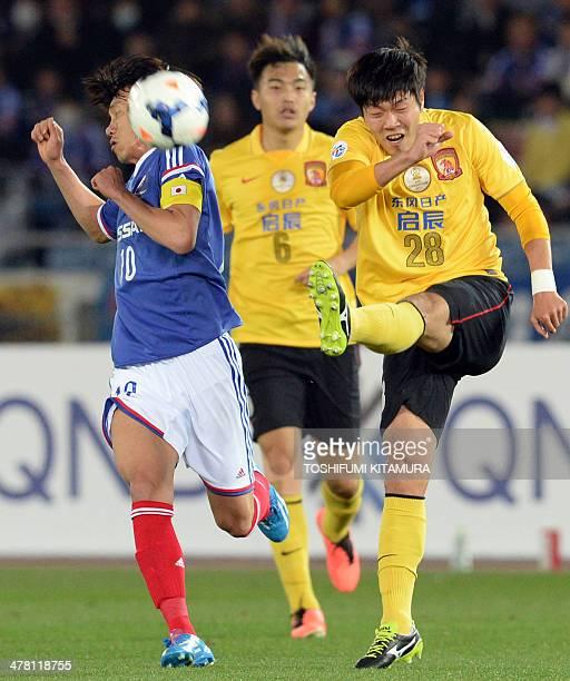 Guangzhou Evergrande defender Kim YoungGwon kicks the ball beside Yokohama FMarinos midfielder Shunsuke Nakamura during their AFC Champions League...