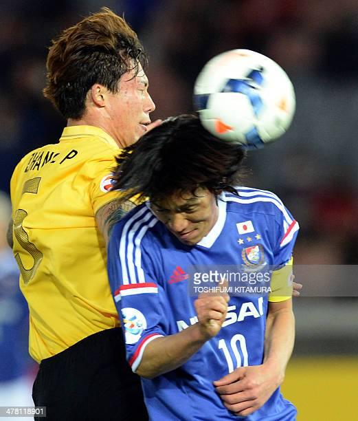 Guangzhou Evergrande defender Zhang Linpeng fights for the ball with Yokohama FMarinos midfielder Shunsuke Nakamura during their AFC Champions League...