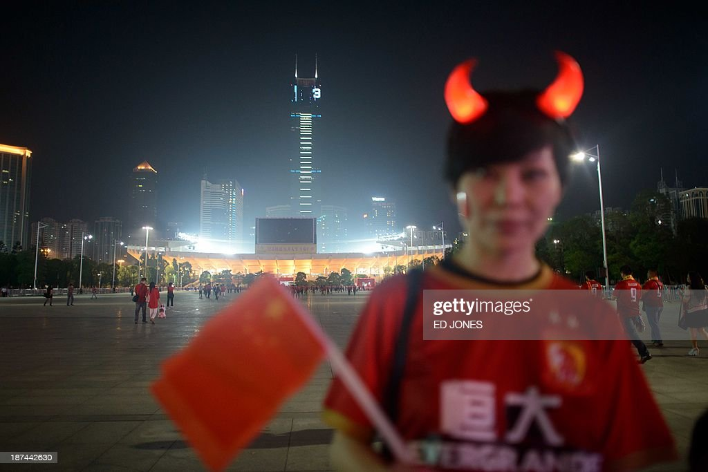 A Guangzhou Evergrande fan holds a Chinese flag as she stands before the stadium prior to an AFC Champions League second leg final football game against FC Seoul in Guangzhou on November 9, 2013. AFP PHOTO / Ed Jones