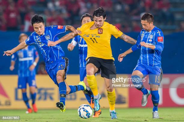 Guangzhou Evergrande midfielder Ricardo Goulart fights for the ball with Gamba Osaka defender Konno Yasuyuki and Gamba Osaka midfielder Omori Kotaro...